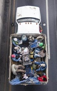 aerial-birds-eye-view-of-people-riding-car-pooling-in-back-of-pickup-trucks-from-above-alejandro-Cartagena-4-186x300