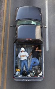 aerial-birds-eye-view-of-people-riding-car-pooling-in-back-of-pickup-trucks-from-above-alejandro-cartagena-2