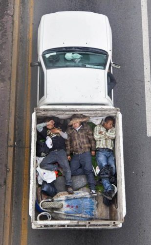 aerial-birds-eye-view-of-people-riding-car-pooling-in-back-of-pickup-trucks-from-above-alejandro-cartagena-6