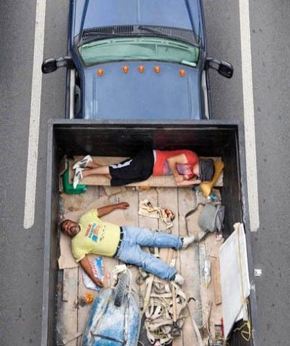 aerial-birds-eye-view-of-people-riding-car-pooling-in-back-of-pickup-trucks-from-above-alejandro-cartagena-7